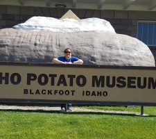 Woman standing in front of a large sign that says Idaho Potato musuem.