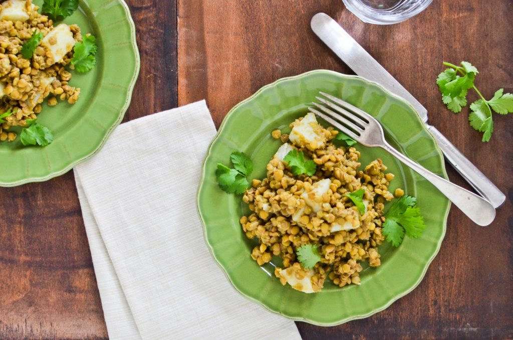 """green plate with lentils on a wooden table"""