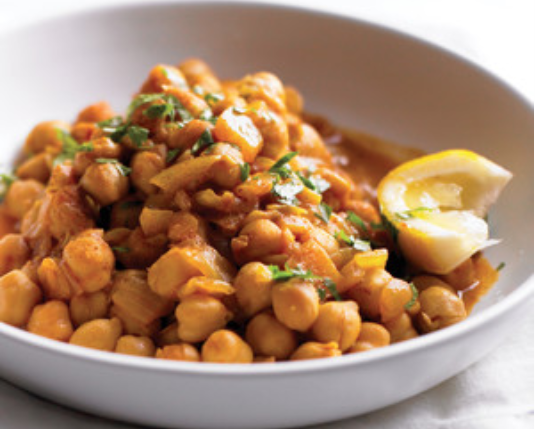 """white shallow bowl with brothy chickpeas and a lemon wedge"""