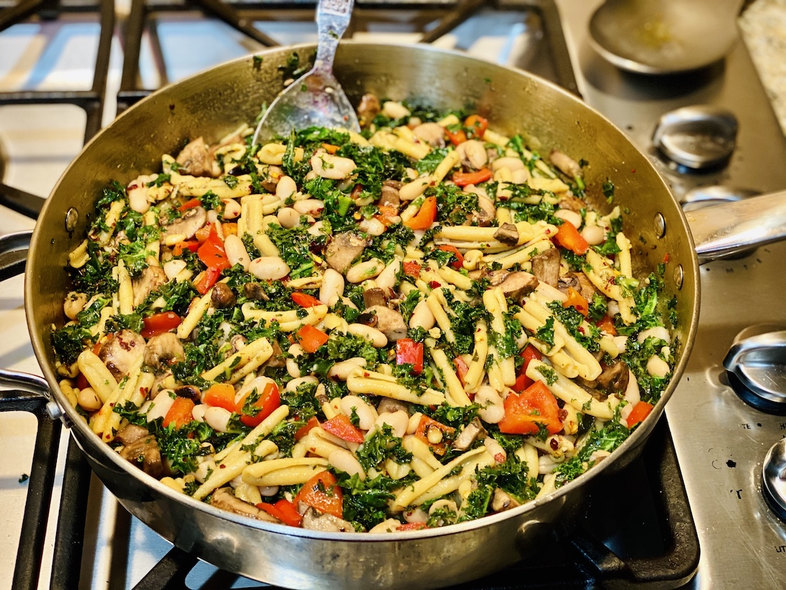 """pan on a gas stove top with kale and white bean pasta"""