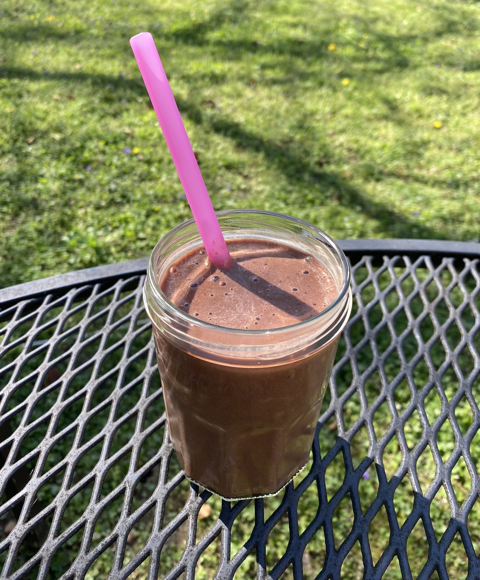 Chocolate banana oat smoothie in a clear glass on an outside table.