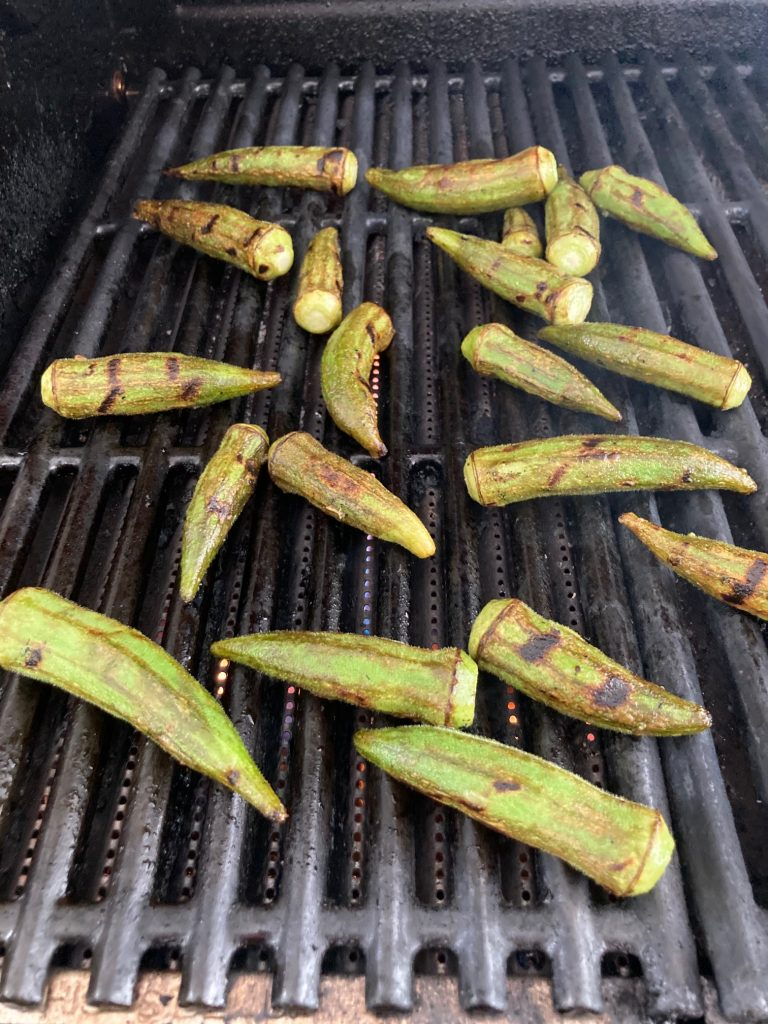 Okra pieces scattered on an outdoor grill top being cooked