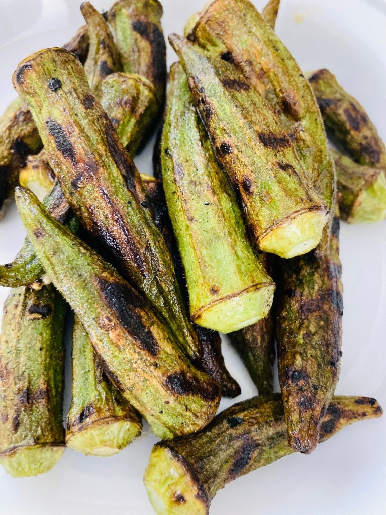 char-grilled okra piled on a white plate
