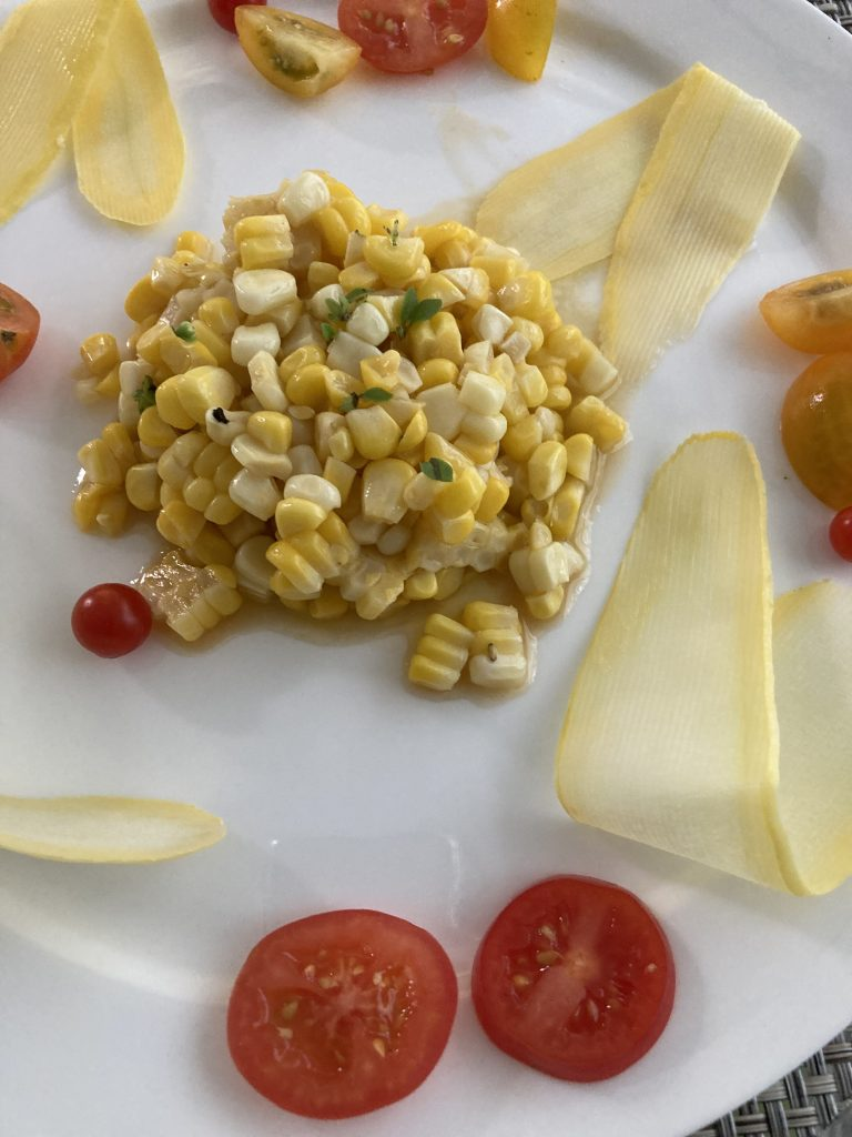 white plate with a scoop of corn salad in the center and squash peels and cherry tomatoes as a garnish