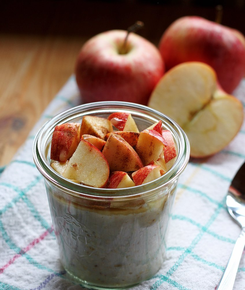 glass jar with overnight oats topped with apples seasoned with cinnamon