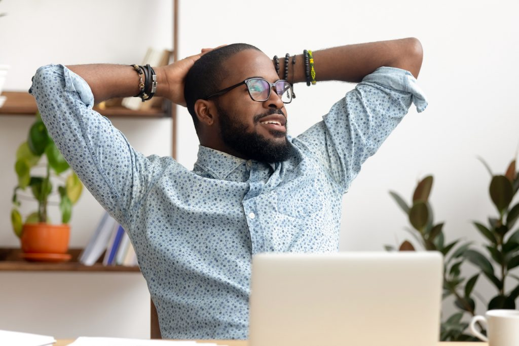 happy black professional enjoying  a rest from his computer screen