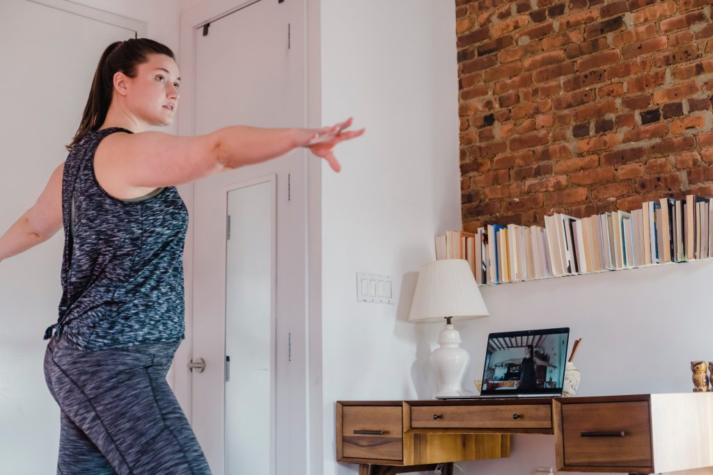 Women in athletic clothing working out in her bedroom using an online exercise class on a laptop
