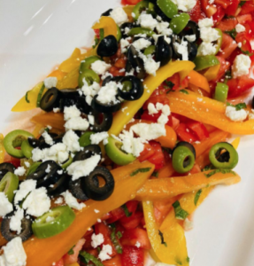Peppers, olives, and feta cheese on a white plate